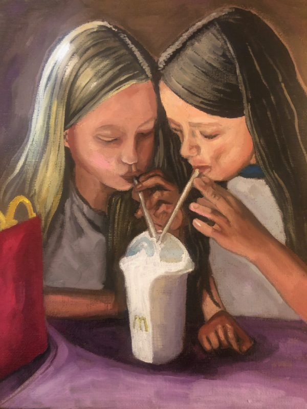 Portrait of two young girls drinking milkshake